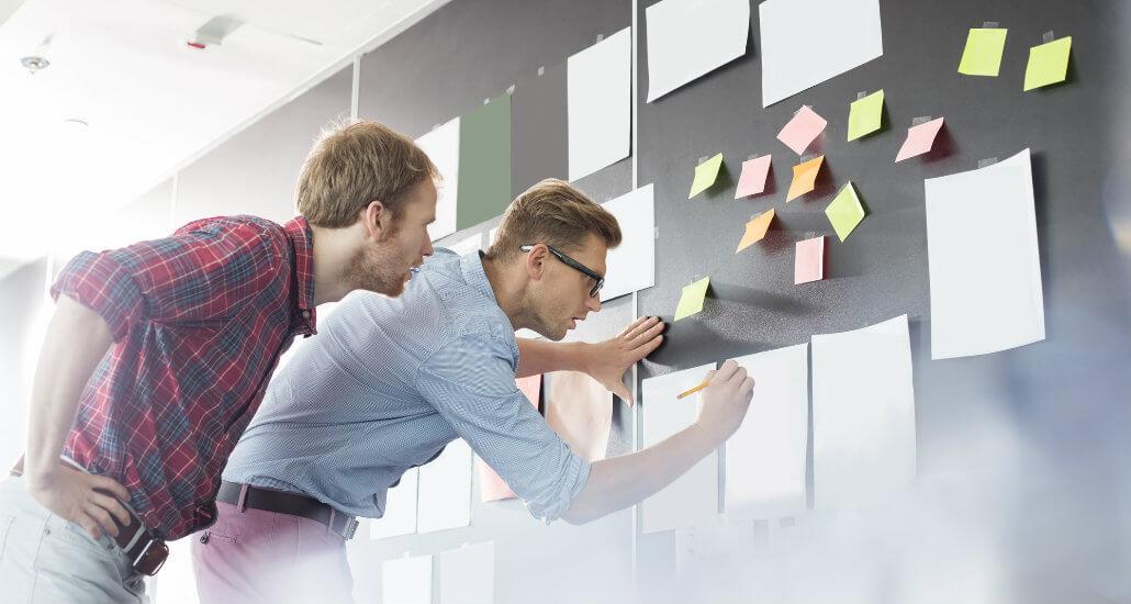 Dois colaboradores criando planejamento em um quadro com papéis colados.