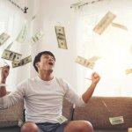 Dinheiro caindo em cima de homem sentado no sofá