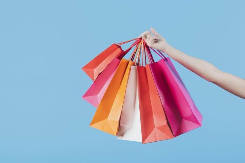 Mão segurando sacolas de compra coloridas