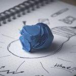Bolinha de papel azul amassada em cima da mesa