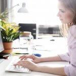 Mulher sentada em mesa em frente a laptop